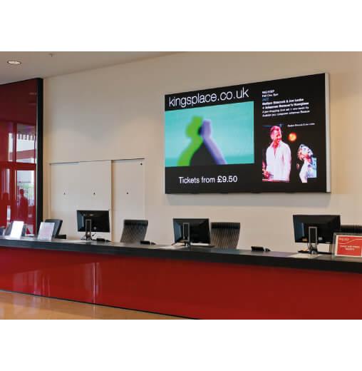 display professionale Sharp serie PN-Q da 70 pollici per desk dietro una reception aziendale