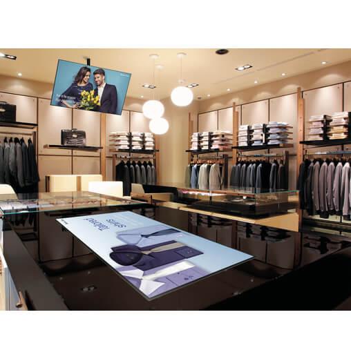 schermo pubblicitario digitale sharp serie PN-R da 90 pollici installato a soffitto e su tavolo all'interno di un negozio abbigliamento
